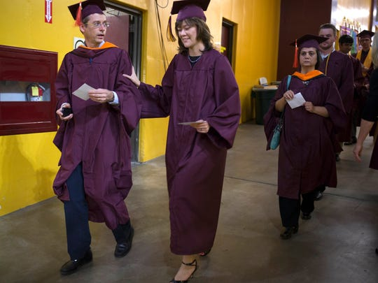 Karl Lauk (left) and his daughter, Stephanie Lauk, walk into Wells Fargo Arena before graduating Tuesday, May 12, 2014, with degrees in electrical engineering from Arizona State University.Karl, 51, is getting a master's degree and Stephanie, 23, is getting a bachelor's degree.