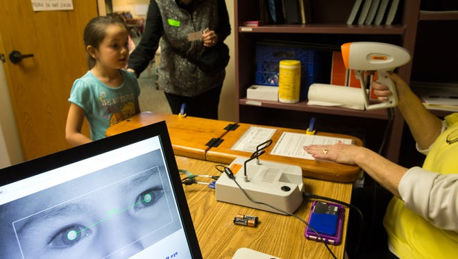 Zoie Herbert has her eyes checked by a scammer held by Farmington Evening Lions Club member Marilyn Montoya, right, on Wednesday at Central Primary School in Bloomfield.