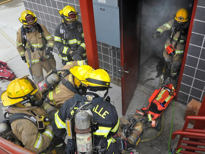 Asheville firefighters drag a 215 pound dummy dressed as a fireman from a smoke filled building during a training exercise at the Buncombe County Fire Training facility in Woodfin. The department has made changes to its approach to fighting fires, including using more firefighter teams to rescue firemen in trouble in burning buildings.