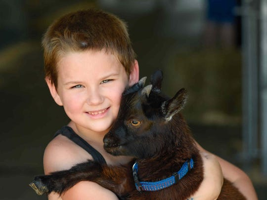 JT Alphin, 6, of Townsend poses for a photo with his goat at the Delaware State Fair in Harrington, Delaware.
