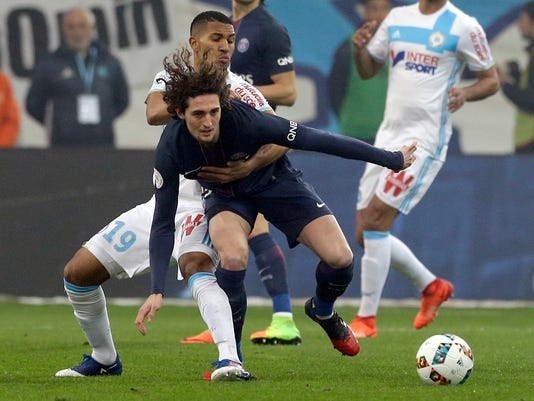 Marseille's William Vainqueur, behind, challenges for the ball with Paris Saint Germain's Adrien Rabiot, during the League One soccer match between Marseille and Paris Saint-Germain, at the Velodrome Stadium, in Marseille, southern France, Sunday, Feb. 26, 2017. (AP Photo/Claude Paris)