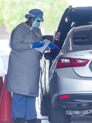 Medical personnel collect saliva samples for coronavirus testing at a drive-up location at Augusta University in Augusta, Ga., Wednesday morning October 28, 2020.