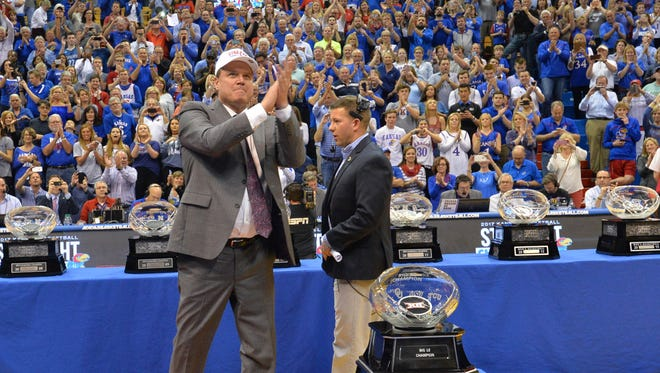 Kansas Jayhawks head coach Bill Self celebrates in front of the Big12 Championship trophy.