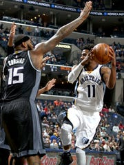 Memphis Grizzlies Mike Conley elevates to shoot while being defended by Sacramento Kings DeMarcus Cousins, left, on Dec. 16, 2016.