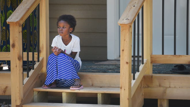 Nema Eliezel sits on the front steps of her family's new home at 503 S. Summit Monday in Sioux Falls. The home is a part of an affordable housing project.