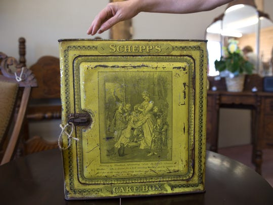 Sandi Harber displays an antique cake box for sale at her store Urban Rebel Antiques on Thursday in Aztec.