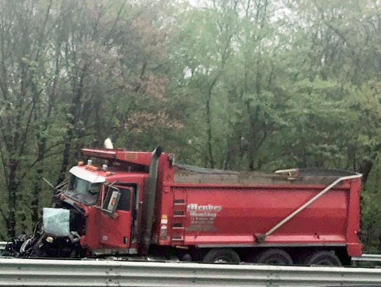 A dump truck sits near the scene after a collision