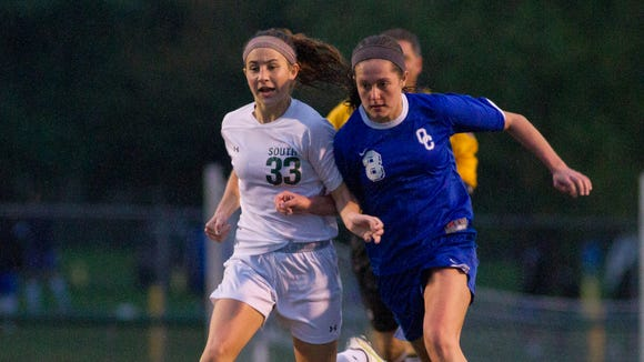 South Oldham's Averi Faulk (33) fights for possesion of the ball against Oldham Co.'s Allie Hoak (8) during the the High School Girls Soccer Semi-Finals at Dragon Stadium. October 15, 2014.