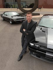 Timothy Kuniskis, President and CEO, Dodge Brand, Fiat Chrysler Automobiles, with his personal 1971 Dodge Challenger, left, and a current production version, right.