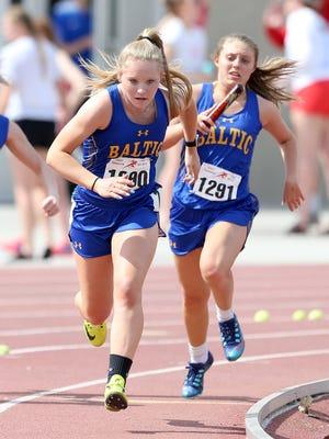 Carrington Entringer (front) and Kelcie Hitzeman (behind) ran with Baltic's 4x100 girls relay team at Howard Wood Dakota Relays on May 5.