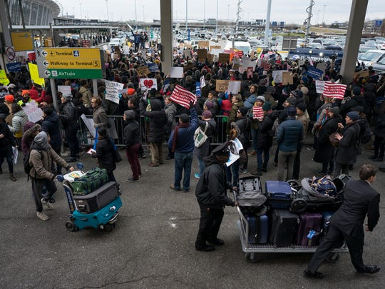 People with luggage walk past protesters assembled at John F. Kennedy International Airport in New York, Saturday, Jan. 28, 2017 after two Iraqi refugees were detained while trying to enter the country. On Friday, Jan. 27, President Donald Trump signed an executive order suspending all immigration from countries with terrorism concerns for 90 days. Countries included in the ban are Iraq, Syria, Iran, Sudan, Libya, Somalia and Yemen, which are all Muslim-majority nations.