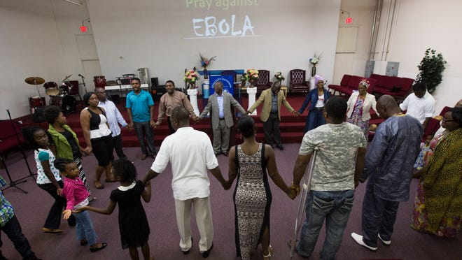 The congregation gathers together to hold hands during a Prayer against Ebola at Africa Faith Expressions Church in Phoenix, AZ on Sunday, Oct. 12, 2014.