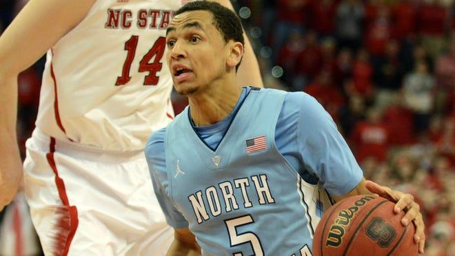 North Carolina guard Marcus Paige drives past North Carolina State center Jordan Vandenberg to score the game-winning basket at PNC Arena.