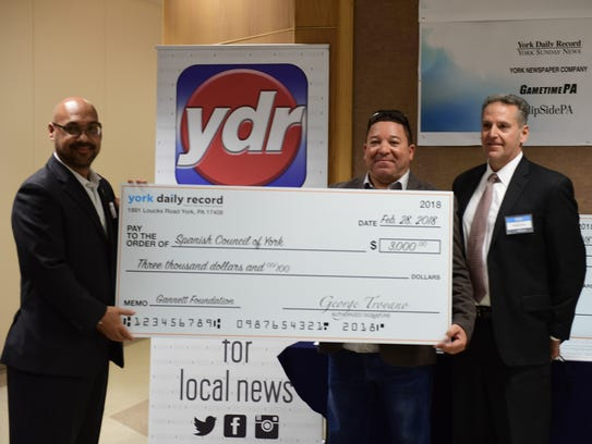 Jose Colon-Bones and Lou Rivera of the Spanish Council of York accept a check for $3,000 from George Troyano, York Newspaper Co. president. The funds were donated by the Gannett Foundation.