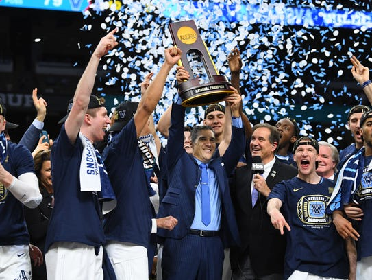 Villanova Wildcats head coach Jay Wright hoists the