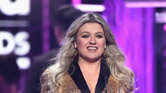 Kelly Clarkson, host of the 2018 Billboard Music Awards, speaks onstage on Sunday, May 20.