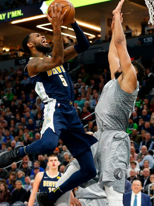 Denver Nuggets' Will Barton, left, shoots over Minnesota Timberwolves' Karl-Anthony Towns during the second half of an NBA basketball game Wednesday, April 11, 2018, in Minneapolis. The Timberwolves won 112-106 in overtime. (AP Photo/Jim Mone)