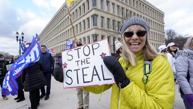 Alyss Kovach holds a sign outside the Richard H. Austin state office building during a rally in Lansing, Saturday, Nov. 14, 2020. Michigan's elections board is meeting to certify the state's presidential election results.