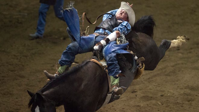 Nick Gutzwiler of Edwall, Washington hangs onto a bucking bronco during the bareback competition during the Larimer County Fair and Rodeo at Budweiser Events Center in Loveland on Monday, August 7, 2017.