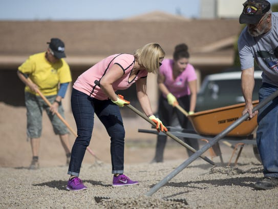 Rep. Kyrsten Sinema (center) and her staff spread gravel on the yard of Ed Mezes on Nov. 21, 2017, in Tempe. The project is part of Habitat for Humanity''s Neighborhood Revitalization Program.