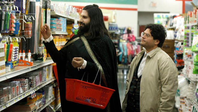 """This image released by FX shows Kayvan Novak and Harvey Guillen, right, in a scene from """"What We Do In the Shadows."""" The series premiering Wednesday is based on the 2014 cult-hit movie from New Zealand."""
