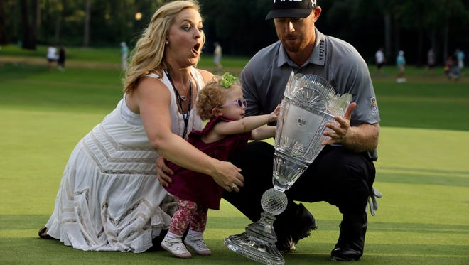 Zoe Mahan, center, pushes the trophy as her mother Kandi Mahan grabs her while they pose with Hunter Mahan, winner of The Barclays on Sunday.