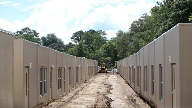 Construction crews work to install portable classrooms at the site of the new Alachua County Public Schools swing school being built in the field at Westwood Middle School off Northwest 35th Street, in Gainesville earlier this week.