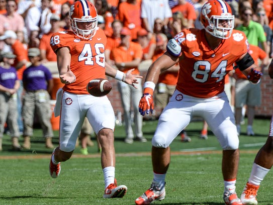Clemson punter Will Spiers (48) punts near tight end