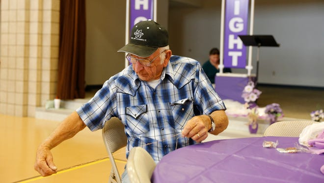 Aztec resident Ernie Phelps unravels a string of lights to decorate tables for a dinner to celebrate cancer survivors on Thursday at First Baptist Church in Bloomfield. The dinner is part of Relay for Life of San Juan County.