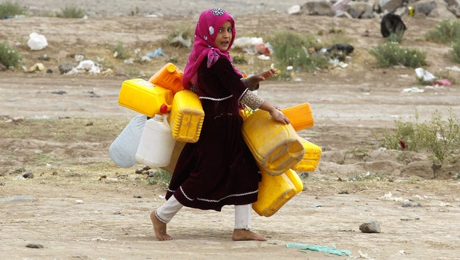 A Yemeni girl carries empty jerry-cans before collecting water from a donated water-tap, on the World Water Day, on the outskirts of Sana'a, Yemen, on March 22, 2017.