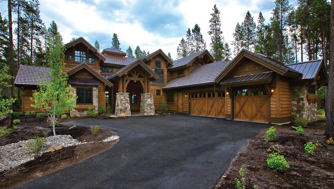 The dramatic entry features double columns atop stone-wrapped bases and an eye-catching truss.