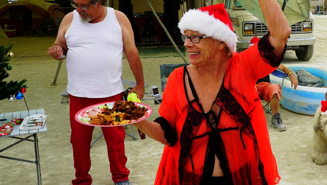 Sunshine Rudiak, dressed in lingerie and a Santa hat, waves to passers-by while offering free fruitcake and Christmas cookies at Burning Man in Black Rock Desert, Nev., on Sept. 3.