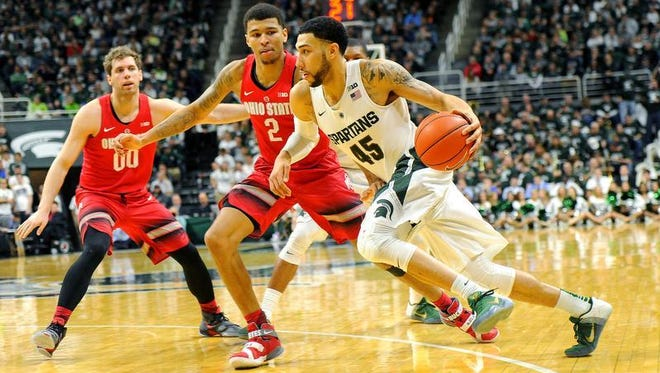 Spartan forward Denzel Valentine drives to the basket against two Ohio State during the Spartans' 91-76 victory over the Buckeyes Saturday at the Breslin Center.