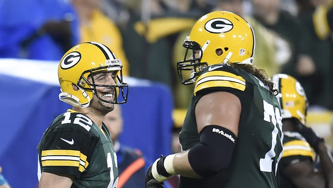 Packers quarterback Aaron Rodgers (12) celebrates a fourth-quarter touchdown with guard Josh Sitton during Monday night's game against the Kansas City Chiefs at Lambeau Field.