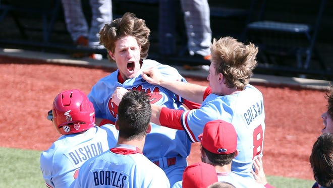 Right fielder Ryan Olenek is mobbed by teammates after hitting a three-run home run to tie Sunday's game against Auburn. Ole Miss won 6-5.