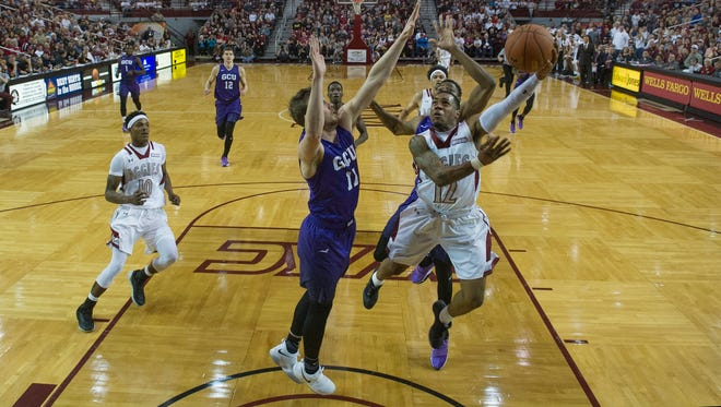 New Mexico State's AJ Harris finishes the fast break around the outstretched arms of Grand Canyon's Casey Benson/