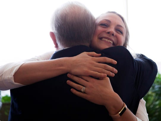 Brittany Sabin hugs George Liberatore during a meeting