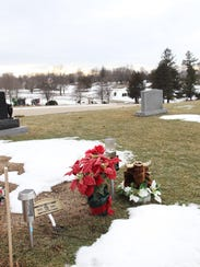 Flowers rest where Tyler Sash is buried at Forest Cemetery
