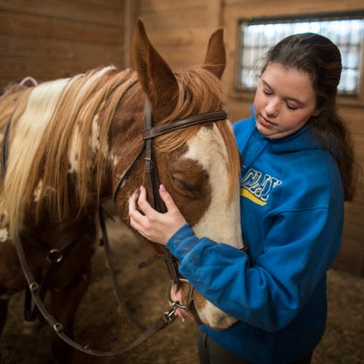 Kaylee Ferrell, 18, gives some love to Passion, the