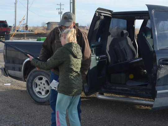 Hunter's Education volunteer Ed Erickson watches as a student checks the action of a shotgun to be sure it is empty. Many accidents that involve firearms occur when a person is taking a rifle or shotgun from a truck so the students in Conrad's Hunter's Education class practiced safe handling until they did it right.