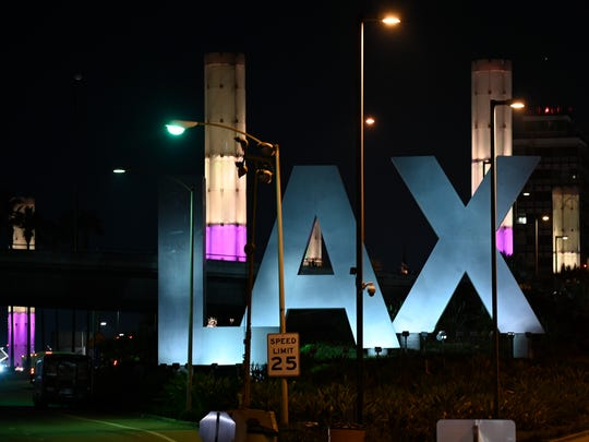 Lights of purple and gold illuminate the pylons outside of LAX in remembrance of former NBA basketball player Kobe Bryant in Los Angeles, Sunday, Jan. 26, 2020, following reports of his death in a helicopter crash in southern California. (AP Photo/Kelvin Kuo)