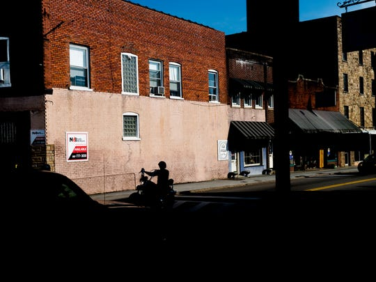A motorcyclist rumbles down Main Street in downtown Clinton, Tennessee on Tuesday, April 3, 2018.