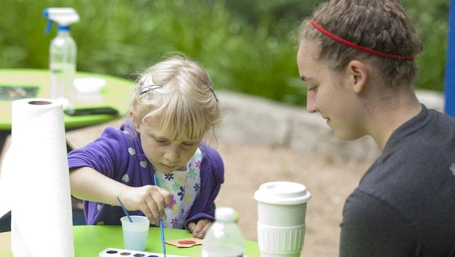 Emma Hersant, 4, of Sheboygan, left, paints with watercolors Tuesday during a Bookworm Gardens Education Station activity. Ali Leonhard, 16, of Sheboygan, helped Hersant understand properties of water.