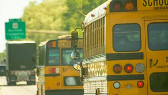 Pair of school buses driving down a highway.