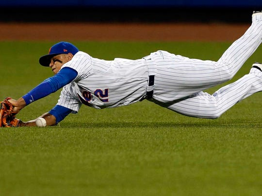 Mets center fielder Juan Lagares (12) misses a ball