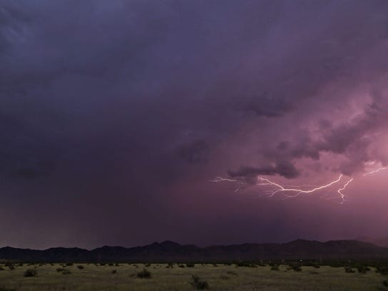 Lightening arcs across the sky over a proposed site