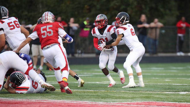 Orrville senior running back Marquael Parks takes a handoff as Northwest's Logan Wise (55) tries to close in during a 2019 game. Parks and the Red Riders are awaiting Northwest in this Friday's season opener.