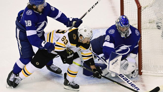 Bruins winger Brad Marchand moves in against Lightning goaltender Andrei Vasilevskiy as Tampa Bay defenseman Mikhail Sergachev (98) defends during the third-period of Monday night's Stanley Cup Eastern Conference playoff game in Toronto.