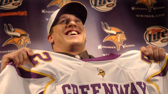 Chad Greenway proudly displays his jersey after being drafted by the Vikings in 2006.