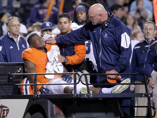 UTEP head coach Sean Kugler comforts running back LaQuintus Dowell after he suffered a serious injury Friday night against Rice, his second injury of the season.